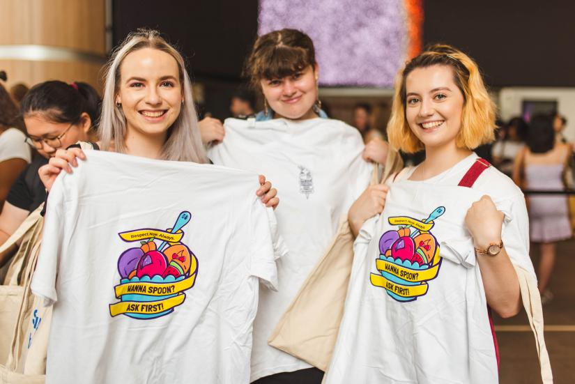three young women holding up Consent Matters tshirts