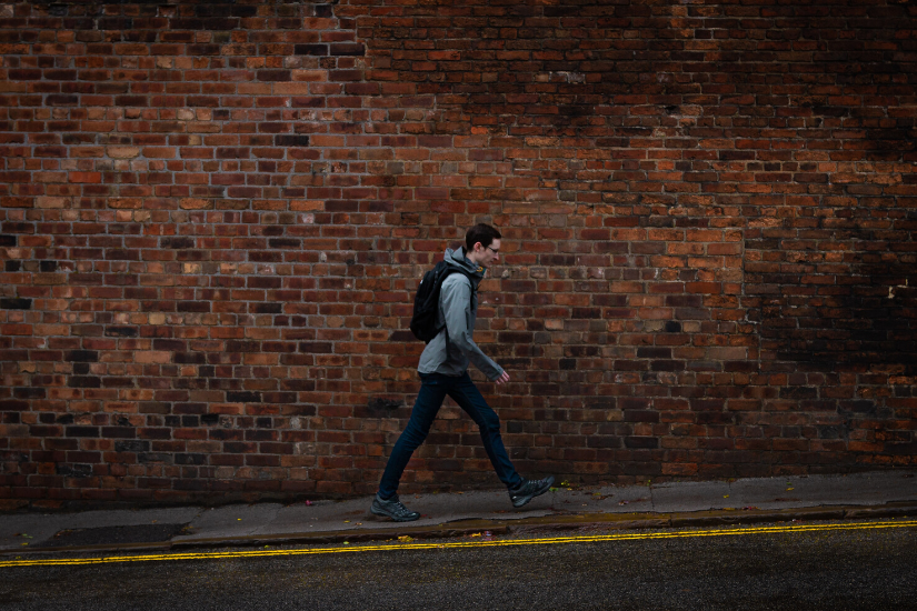 Lonely man with backpack walking on street with brick background.