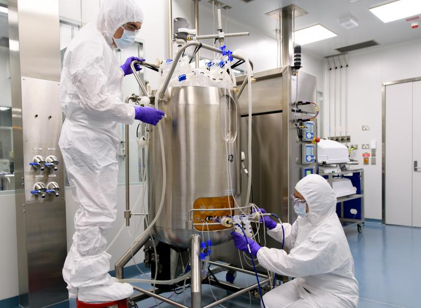 Two process engineers operating an Xcellerex XDR-200 single-use stirred-tank bioreactor while adjusting tubing and sensors.