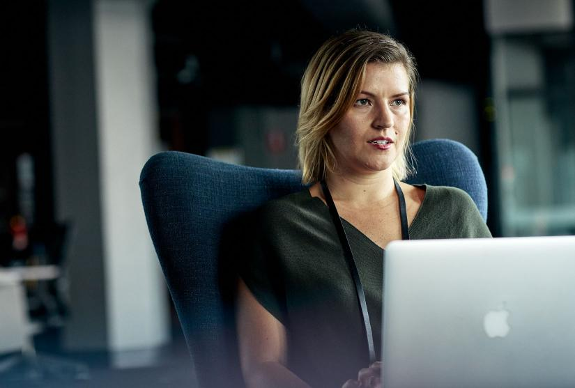Woman in green blouse on apple laptop