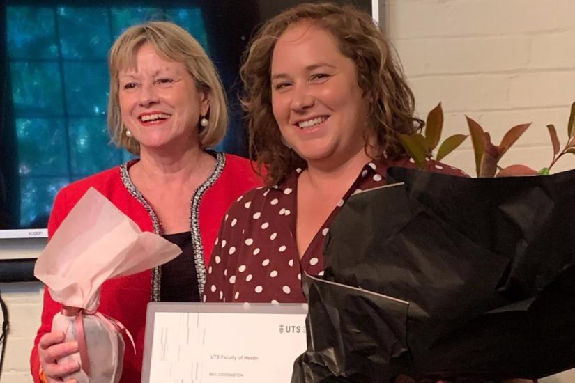 Two women smiling, receiving an award