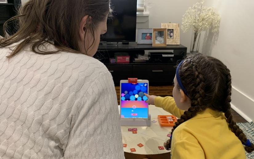 A child plays a maths game on an iPad.