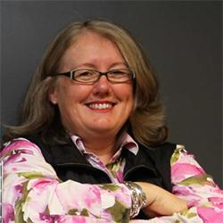 Dist Prof Mary-Anne Williams, wearing glasses, smiling with arms crossed, in floral shirt and black vest