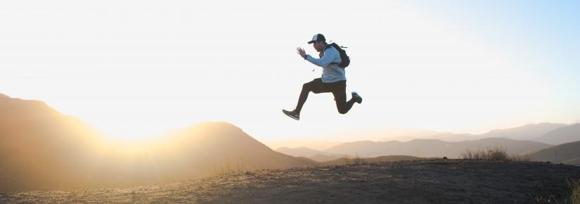 person jumping on a mountain