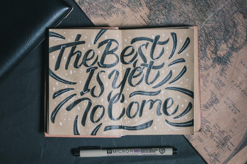 Open book seen from above showing handwritten text The Best is yet to Come
