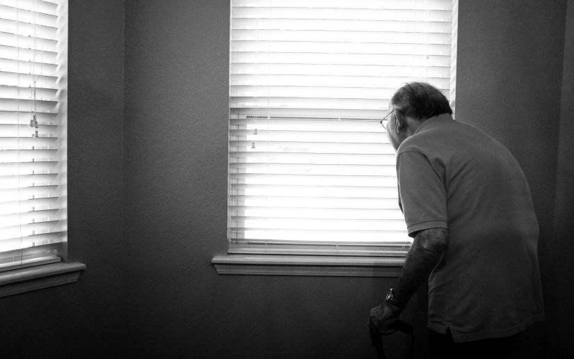 An elderly man in a white room near two windows.