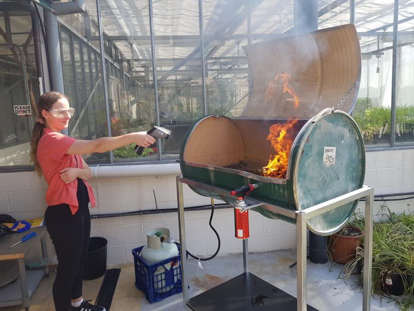 Molly Wallace, Master of Science student, using an IR gun to measure the heat released when burning plants.