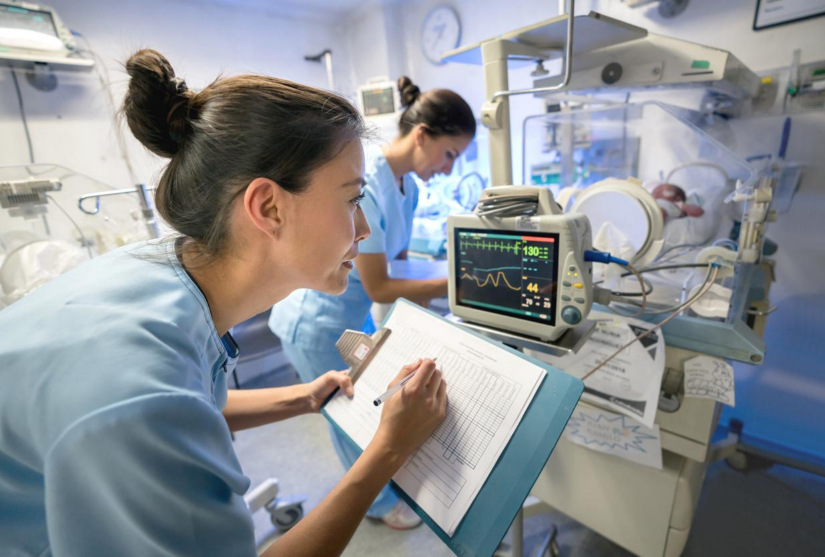 Nurse recording patient information on chart