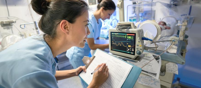Nurse recording patient information on chart