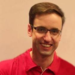 Dr Benjamin Johnston smiling, wearing a red t-shirt