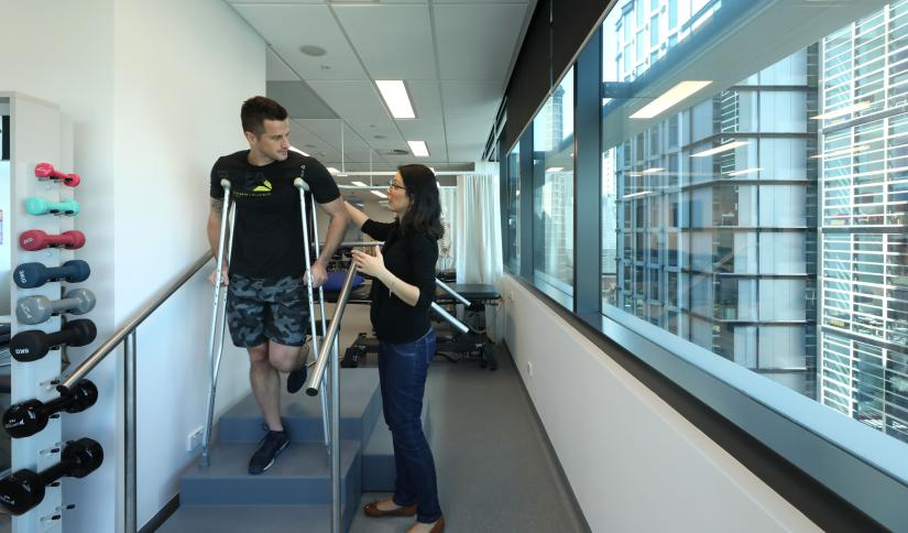 man on crutches talks to physiotherapist