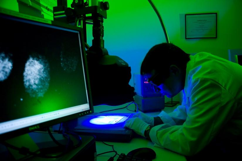 photo of a man in lab coat looking though a microscope in a darkened science lab