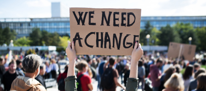A protester holds a sign reading 'We need a change'