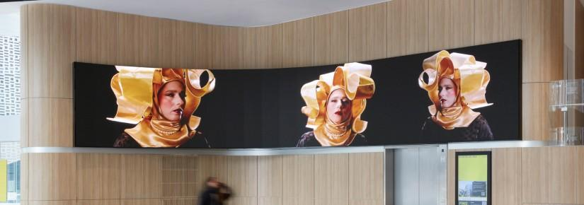 An artwork on the Broadway Screen, featuring a woman in an extravagant gold headscarf, repeated three times on the screen