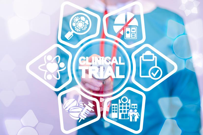 Medic in scrubs in background with graphics overlaid including the words clinical trial and surrounded by related medical icons