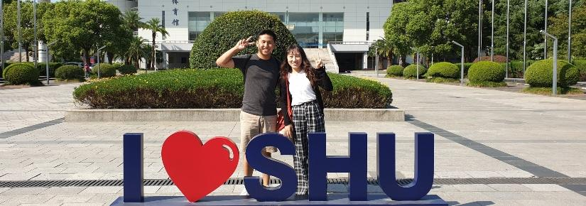 two students standing behind a sign that says i love shanghai university
