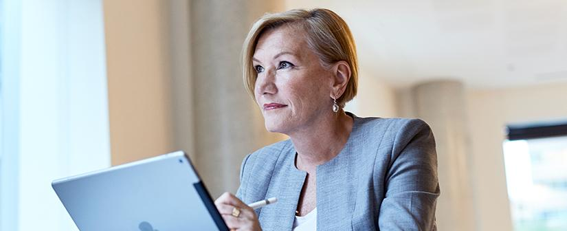 Lady holding an iPad and looking into the distance