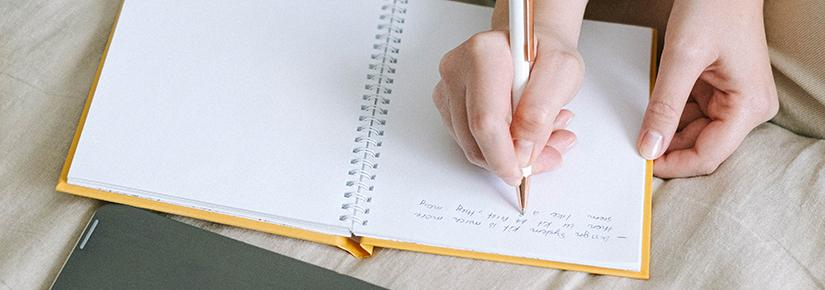 A birds eye view of a hand holding a pen and witing on a book