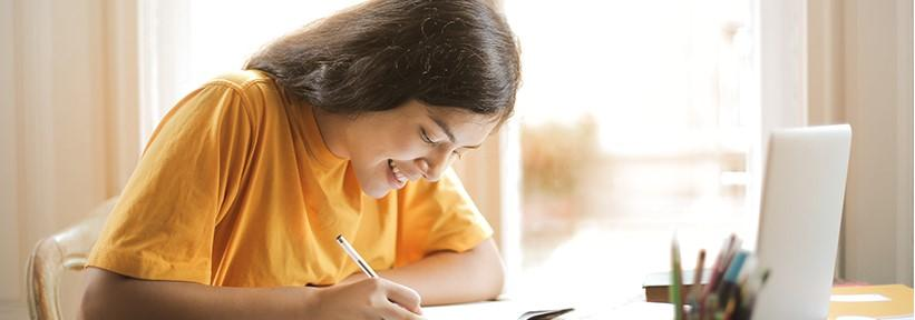 A girl in a yellow shirt studying and writing in a book