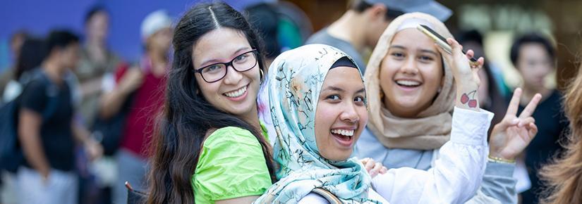 Three girls smiling on campus