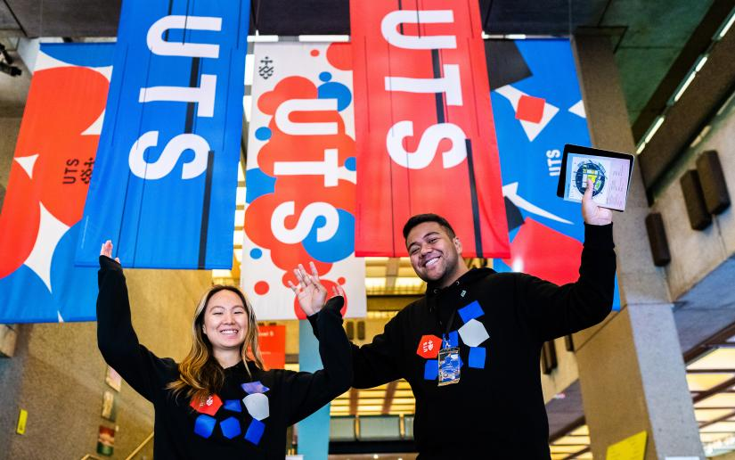 Two UTS students stand in front of UTS banners at Open Day.