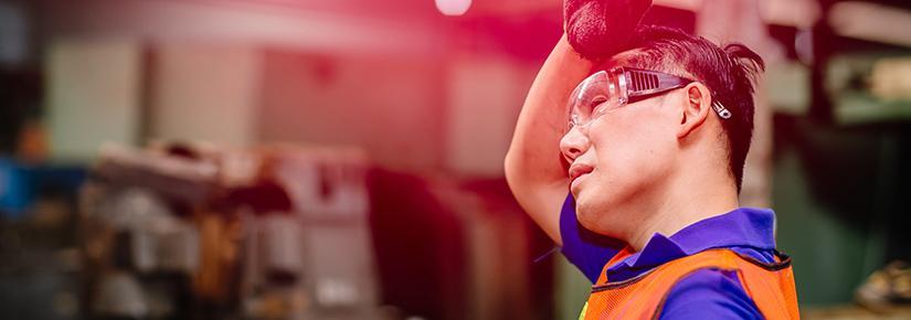 Sweaty worker mops his brow