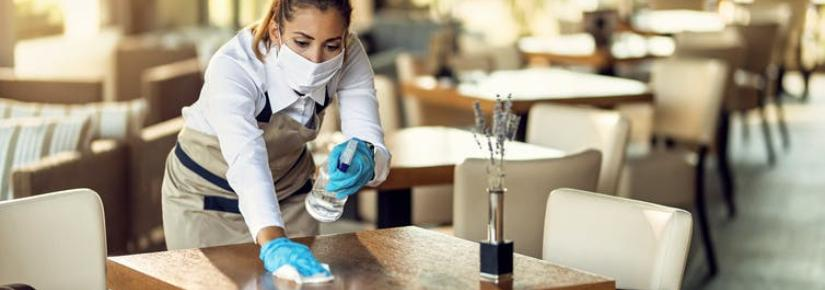 a waitress in a mask and gloves cleans a table