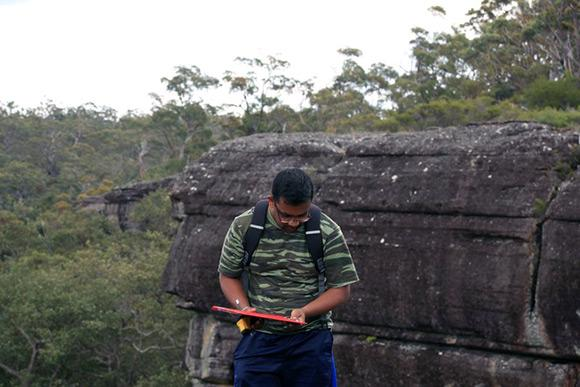 PhD student Buddhi Dayananda in the field at Morton National Park