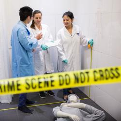 Three students in mock crime scene