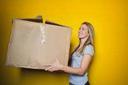 Young blonde, fair woman carrying large cardboard box against yellow background