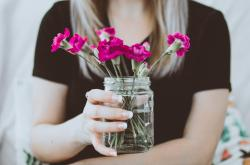 Deep pink flowers sitting in a glass jar being held by a blonde woman wearing a black t-shirt