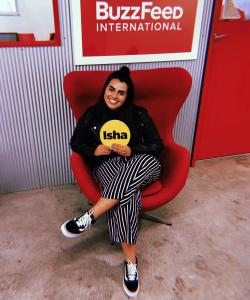Isha sitting on a red chair in the BuzzFeed office