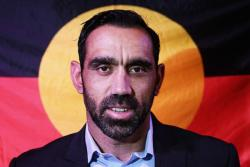 Photo of Adam Goodes in front of the Aboriginal flag