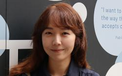 Photo of Sejeong Kim in front of a UTS mural