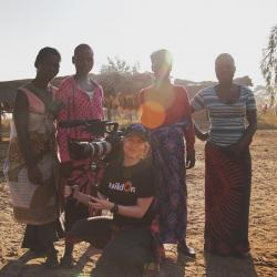 Christel with camera filming locals in Africa