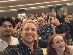 Hamish Macdonald taking a selfie in front of an audience