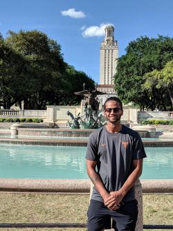 Abhi standing out the front of University of Texas at Austin