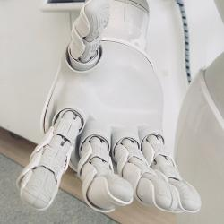 White robotic hand reaching out towards the camera