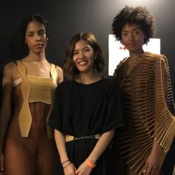 Jessica Xie smiling, between two models wearing looks from her fashion collection.