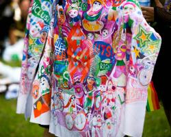 UTS Mardi Gras 2018 design, printed on fabric worn as a cape. The design features bright colours, and includes the UTS logo, faces and text.