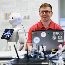 PhD student Sammy Pfeiffer with Pepper robot behind a desk of IT equipment at The Magic Lab