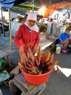 A woman in a market in Indonesia selling dried fish