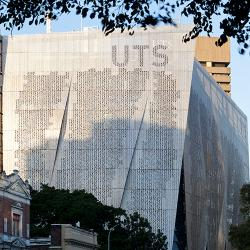 A large, rectangular building covered in aluminum screens with a perforated binary code