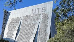 A shiny, aluminum clad building perforated with holes with a UTS logo at the top
