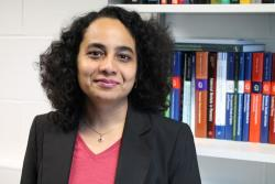 A picture of A/Prof Arti Argawal standing in front of a book shelf