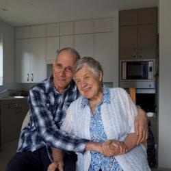 Happy older couple hugging in a kitchen