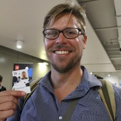 Dr Chris Brummer holds his new UTS card