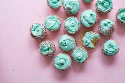 Cupcakes with blue icing and sprinkles on a pink background.