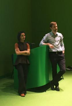 Pavlina Naydenova and James Tilbury leaning against green lectern.
