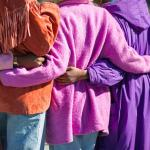 Three people wearing purple with their arms around each other.